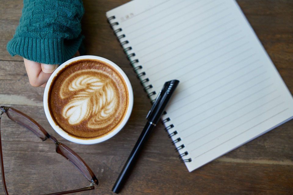 Cup of coffee next to notepad