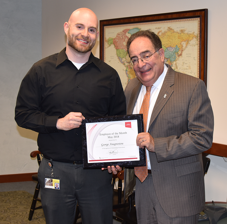 Employee of the Month George Anagnostou recieves a certificate from UMB's president.