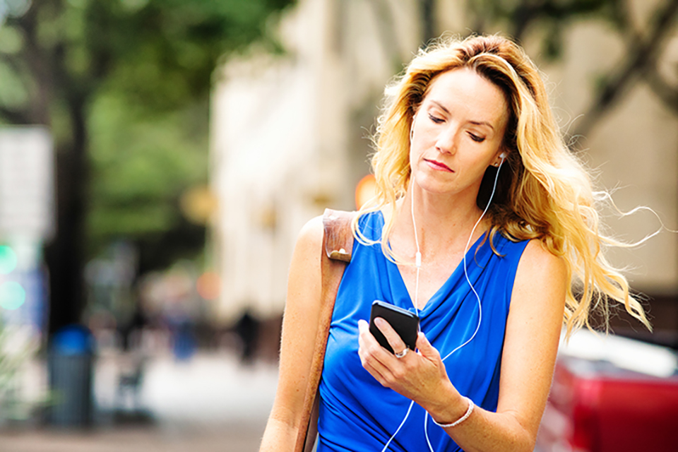 Woman wearing earbuds and looking at cellphone