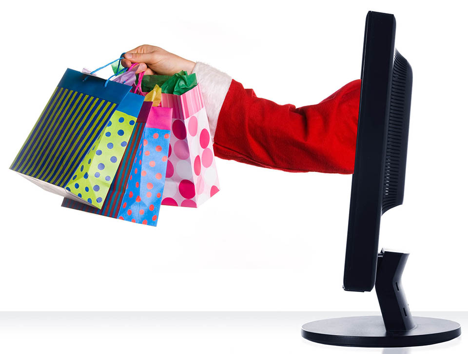 Santa Claus sticking hand out of monitor with gifts